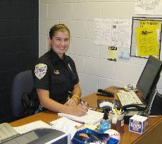 Female officer smiling at desk
